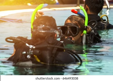 Scuba diving instructor and student in a swimming pool.(With warm sunlight effect and selective focus)