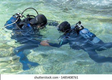 Scuba Diving Instructor Teaching a Little Boy to Dive. Junior Open Water Diver Course. Instructor Giving Scuba Diving Lessons to a kid. Two Scuba Divers in Shallow Sea.
