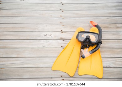 Scuba diving mask and fins on the wooden board