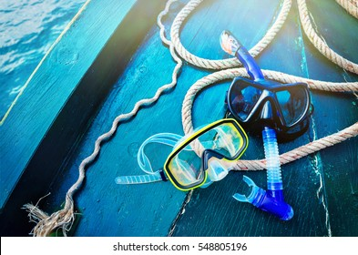 Scuba diving and snorkeling. Two snorkel on blue wood background. The deck and the nose of the ship with a solar glare