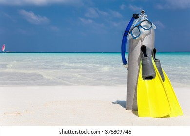 Scuba diving tank, fins and mask on a beach