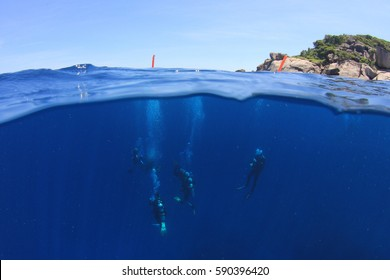Scuba diving underwater. Over under half and half split photo. Ocean, surface, sky and island