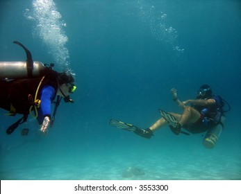 A scuba instructor guides a student