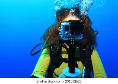 Scuba woman with action camera underwater in the sea