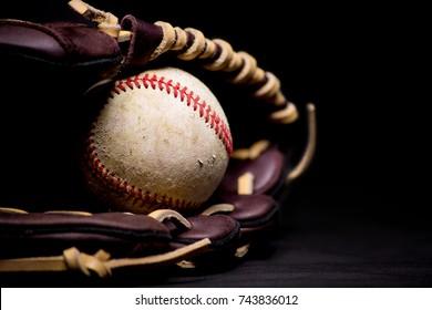 Scuffed up baseball inside brown leather baseball glove