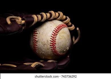 Scuffed casing on baseball sitting inside leather glove.