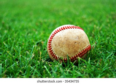 Scuffed old baseball on the grass