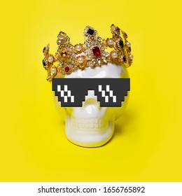 Scull in pixel glasses and crown on a yellow background. Minimal concept art.