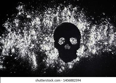 Scull shaped of sprinkled white powder on black background. Sign of danger or drug addiction.