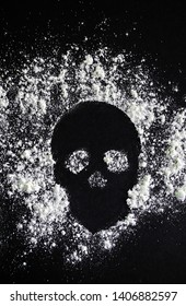 Scull shaped of sprinkled white powder on black background. Sign of danger or drug addiction.