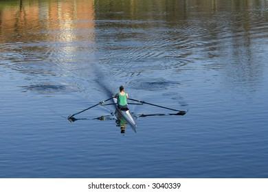 Sculler or rower on River Clyde in evening sunshine, Glasgow