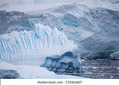 A sculpted iceberg with a glacial background