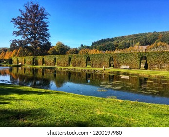 Sculptered hedge and water at the garden of Annevoie in autumn in Belgium