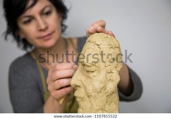 彫刻家が粘土でバスト彫刻を作る。彼女は仕事に満足し、集中し、女性を ...