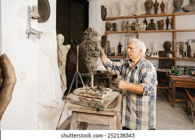 Sculptor creates head in a studio