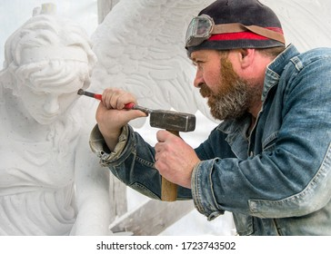 The sculptor cuts an angel sculpture from white marble.