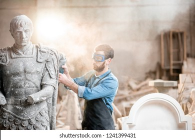 Sculptor in protective workware grinding stone sculpture with electirc grinder in the old studio with dust