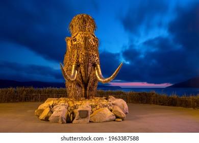 """Sculptural composition """"Time"""", Magadan, Magadan Region, Far East of Russia - September 27, 2018. Modern sculpture. A mammoth made from scrap metal. Evening landscape. Tourist attraction of Magadan."""
