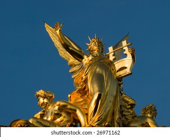 Sculptural detail on the roof of the Opera Garnier, Paris - Closeup of a golden statue of a female angel holding a Harp surrounded with two others angels.