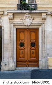 Sculptural entrance arch and antique double door with round framed door windows of old building in Paris France. Vintage wood doorway and ornate stone wall of ancient house at street of city in Europe