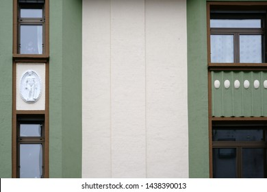 The sculptural reliefs of two Greek Roman figures on the facade of an old residential house.