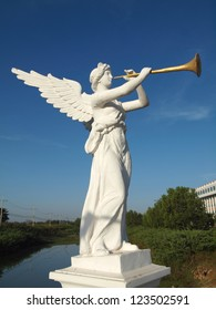 a sculpture of angel blowing golden horn