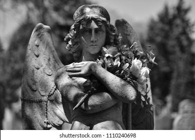 Sculpture of an angel with flowers in her hand on a grave of the cemetery of Montreal-Canada