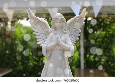 Sculpture of an angel in the garden with bokeh.