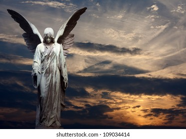 Sculpture of angel on cemetery in sunset background