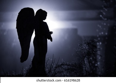 A sculpture of an angel with scary background