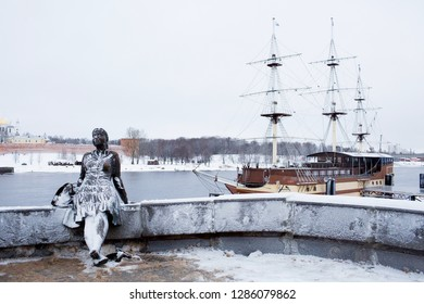 Sculpture of a bronze girl and a flagship frigate, a restaurant on the waterfront on a winter cloudy day. View from the bridge. Veliky Novgorod, February 2018