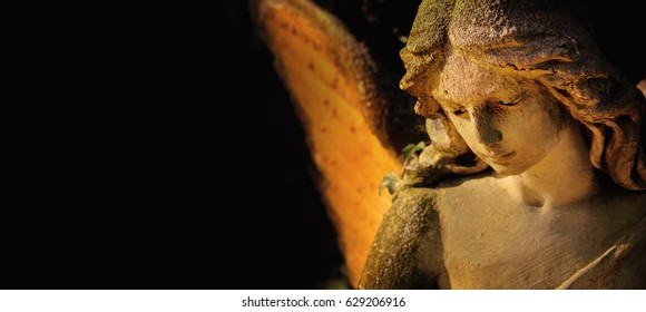 sculpture of gold angel with wings against dark background