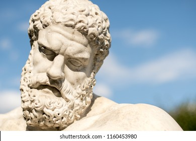 Sculpture head, bearded face of Heracles - Greek mythology God of strength, heroes, health with blue sky in background