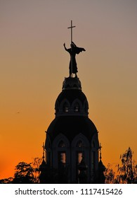 Sculpture of John the Baptist on the temple in Dnepropetrovsk (Ukraine), silhouette at sunset