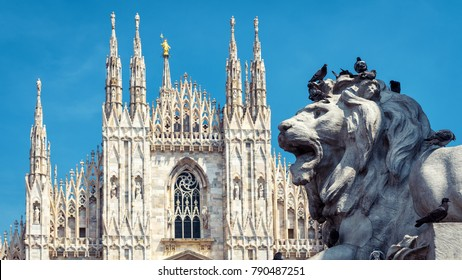 Sculpture of a lion on Piazza del Duomo, Milan, Italy. Duomo di Milano or Milan Cathedral in the background. It is a largest church in Italy and Milan landmark. Historical architecture of Milan.