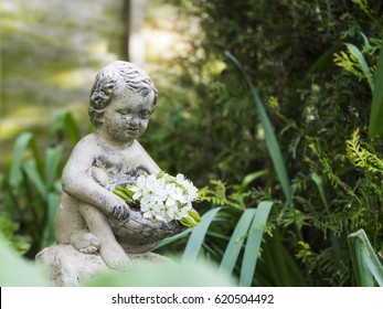Sculpture of a little boy with white flowers on his hands in english garden
