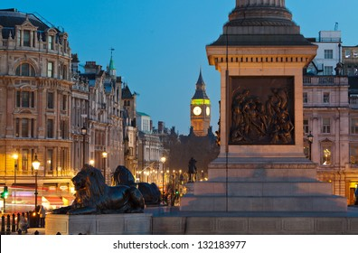 Sculpture lying lions at Nelson's Column pedestal in Trafalgar Square. Whitehall Street and Big Ben in the distance. Twilight