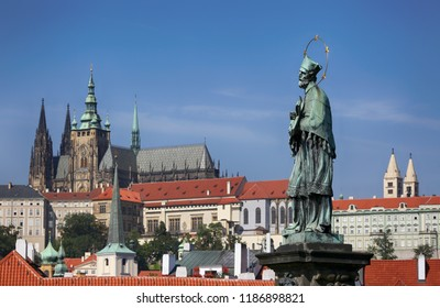 Sculpture on the Charles Bridge on the background of the sky and Prague Castle