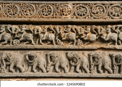 Sculpture on temple wall - elephants, horses and foot soldiers on the wall of an ancient Hindu temple.