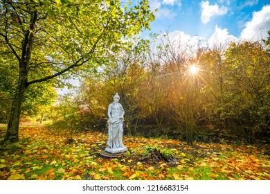 Sculpture in a park with colorful autumn leaves on the ground in the fall