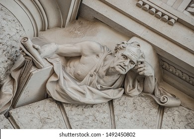 Sculpture of strange and awkward people of Renaissance Era as support for building facade in Vienna downtown, Austria