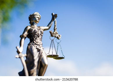 sculpture of themis, femida or justice goddess on outdoors bright blue sky copy space background
