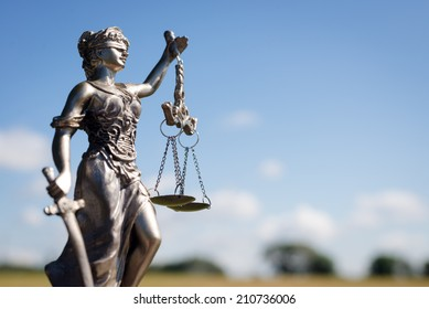 sculpture of themis, femida or lady justice goddess on bright blue sky copy space background
