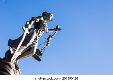 sculpture of themis greek goddess symbol of justice on blue sky copy space background