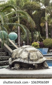 Sculpture of a turtle on a background of palms