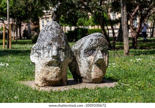 Sculpture two stone heads in the park near King Peter I Square. Serbia, Pancevo, May 15, 2021