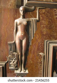A sculpture of a woman, made in bronze with marble on the background