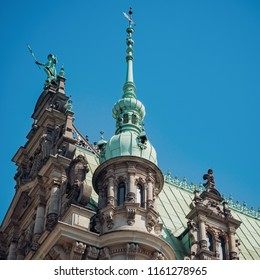 Sculptures on the top of Rathaus on the blue sky background. Rathaus is the famous Hamburg City Hall, Germany.