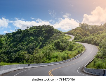 S-curve road up to the hill with Green tree and sky at Nan province Thailand