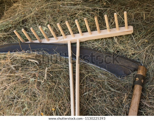 A scythe and a rake with  hay